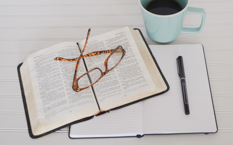 This is a picture of an open Bible with a pair of glasses, a journal and a cup of coffee.